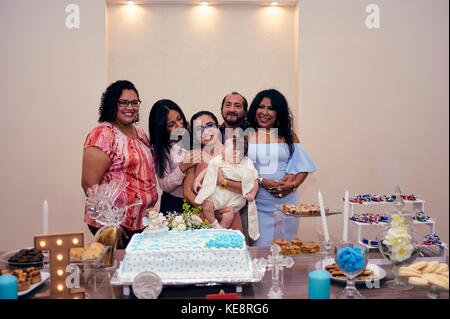 Guests having their picture taken with the just christened baby at his baptismal party - Stock Photo