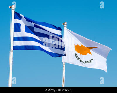 The flags of Greece and Cyprus flutter against a blue sky in Paphos Cyprus. - Stock Photo