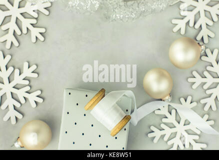 Gift boxes wrapped in silver paper. Wooden spool with white curled silk ribbon, Christmas baubles, snow flakes arranged - Stock Photo