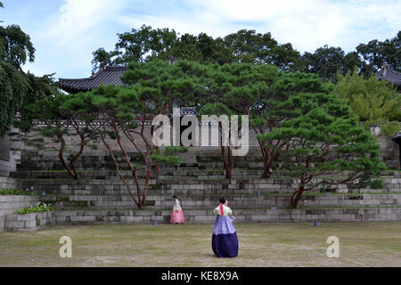 Girls in traditional clothes taking photo in front of trees around Seoul Eastern Palace (Changdeokgung). Pic was - Stock Photo