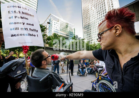 Disability campaigners protest outside the Crossrail head office building in Canary Wharf, London, UK. - Stock Photo