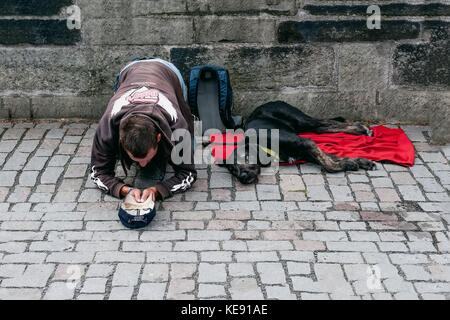 Prague 13.08.2013. A homeless young man with a big black dog on the street asking passersby for money. The horizontal - Stock Photo