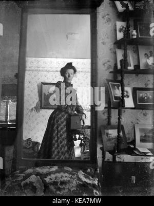 Unidentified woman taking her own photograph using a mirror and a box camera, roughly 1900 - Stock Photo