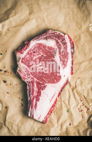 Raw steak rib-eye with seasoning on craft paper, copy space - Stock Photo