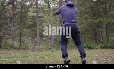 A young athletic man jumping, performs strength exercises, a crossfit element. In pine forest, summer - Stock Photo