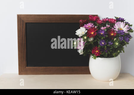 flowers in vase and blank board - Stock Photo