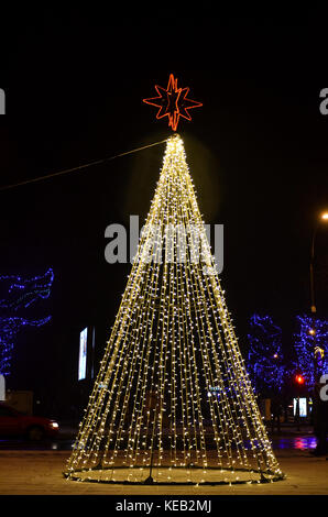 isolated Christmas tree decorated with lights at night outdoor in street - Stock Photo