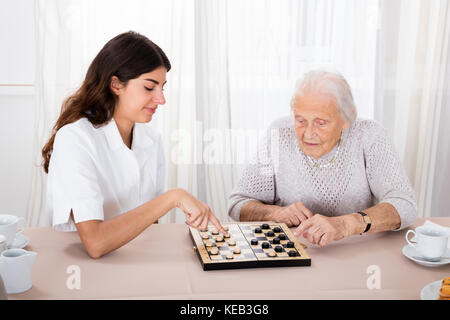 Senior Woman Playing Checkers Game With Young Nurse On Table - Stock Photo