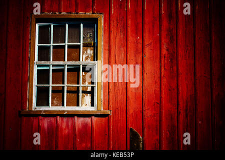 Abandoned house with old peeling red wooden wall and grunge broken window under dramatic lighting producing a scary - Stock Photo