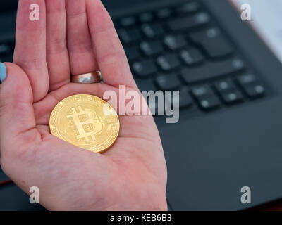 Woman holding in hand golden bitcoin close up - Stock Photo