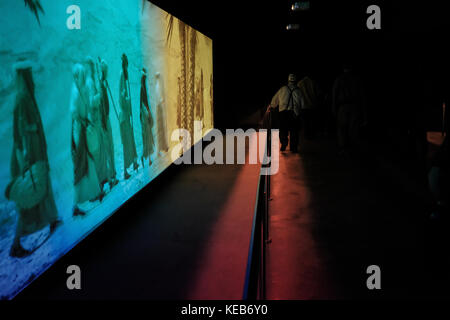 Visitors enjoy instruction from a  guide in a traditional costume, a 3D video experience and light and sound exhibits - Stock Photo