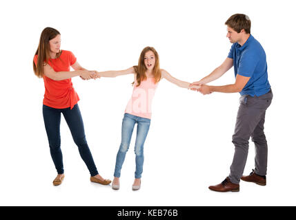 Unhappy Couple Pulling Their Daughter On Their Side On White Background - Stock Photo