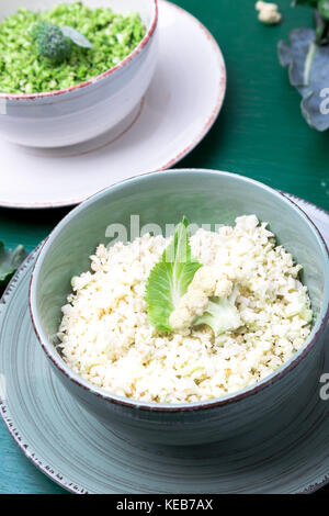 Cauliflower rice and broccoli rice in bowl on green background. Shredded - Stock Photo