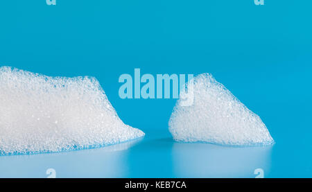 White soap bubbles foam on blue background. Suds shower texture macro view photo, shallow depth of field - Stock Photo