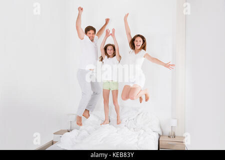 Happy Family Jumping On Bed Together In Their Bedroom - Stock Photo