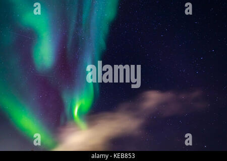 Green Northern Lights glowing in the sky among the stars and clouds, Nuuk, Greenland - Stock Photo