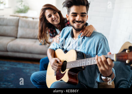 Young handsome man playing guitar for his girlfriend - Stock Photo