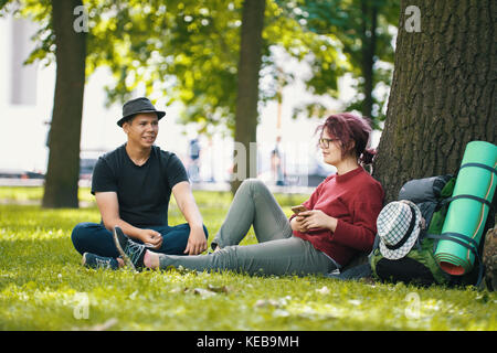 Couple of teenagers tourists with backpacks have rest in the city park near big tree - Stock Photo