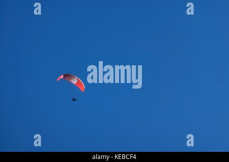 Paraglider against blue sky at Chamonix Mont Blanc over the Aguille du Midi, France - Stock Photo