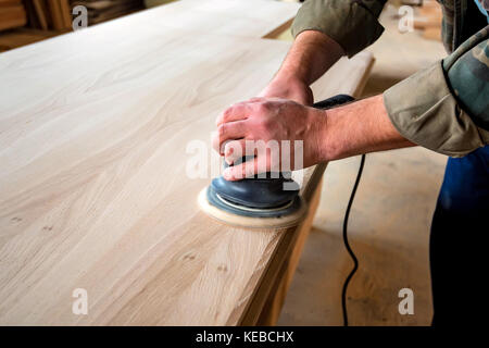 Man sanding wood with orbital sander in a workshop - Stock Photo