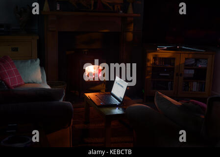 Working from home by the fire in the early evening and into the night at the computer to finish a project. - Stock Photo
