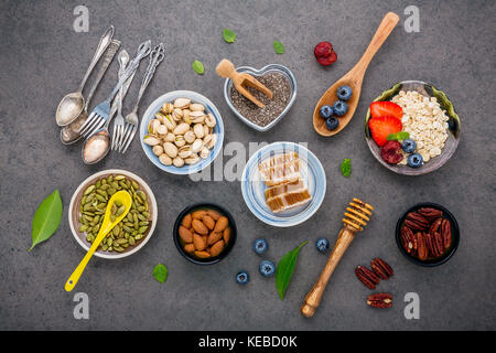 Ingredients for the healthy foods background Mixed nuts, honey, berries, fruits, blueberry, orange, almonds, oatmeal - Stock Photo