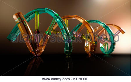 Plastic transparent double helix model with DNA coding - Stock Photo