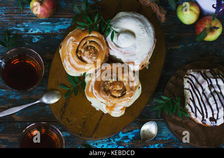 Fresh baked cinnamon rolls with frosting, apples and tea on the shabby background. View from top - Stock Photo