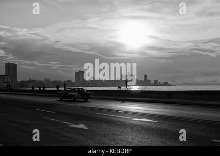 Documentary travel image taken on The Malecon seawall, shadowy figures at leisure walk along, a classic Cuban car - Stock Photo