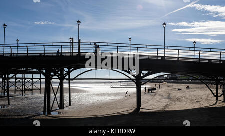 People walk over Cleethorpes Pier in background boy plays with football past donkeys. England, UK - Stock Photo