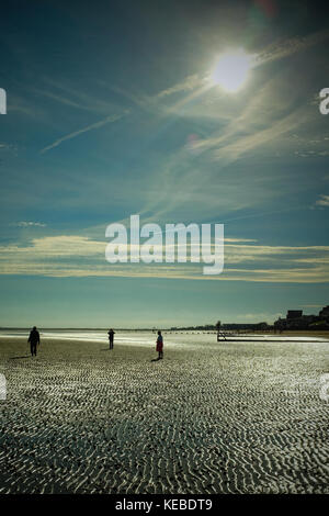 Three silhouetted figures at low tide on Cleethorpes seafront. East coast of England, UK - Stock Photo