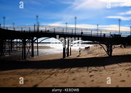 Jogger exercising on beach runs under Cleethorpes Pier, East Coast of England, UK - Stock Photo