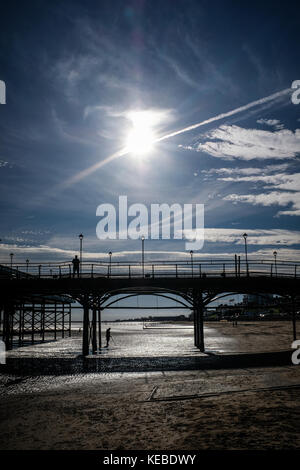 Metal detecting under Cleethorpes Pier, man stands above, silhouetted photograph - Stock Photo