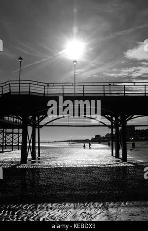 Tourists walking out to waters edge past silhouetted Cleethorpes pier - Stock Photo
