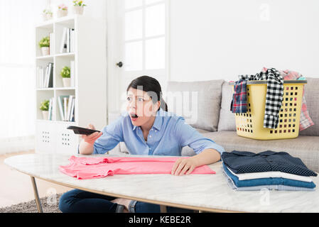 young beauty woman holding television remote control choosing program and looking at shocked news showing surprised - Stock Photo
