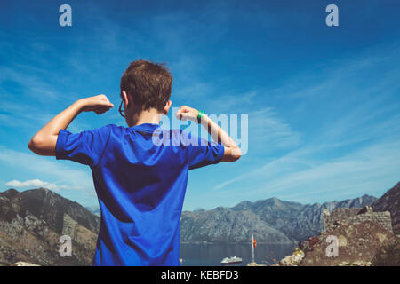 The view from the fort above Kotor after a long climb with a boy in the foreground showing his muscles - Stock Photo