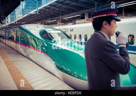 On Japan Railways both the trains and the service are polished. A shinkansen leaves Tokyo Station with a guard in - Stock Photo