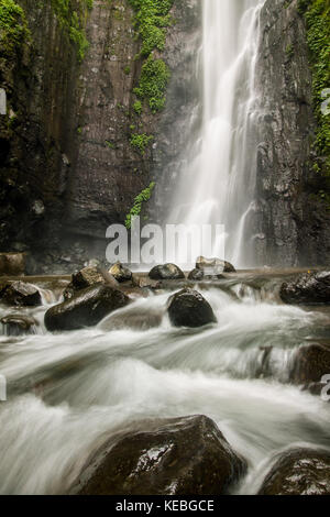 Silky smooth Waterfall landscape with long exposure photography creating an idyllic nature scene in the Javanese - Stock Photo