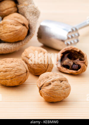 Walnuts kernels and whole walnuts on wooden background. Whole and chopped walnuts on wooden background. Walnuts - Stock Photo