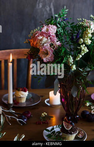 The beautiful rustic bouquet of flowers on festive table - Stock Photo