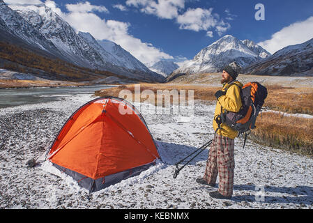 Hiker with backpack at camping in the mountains during springtime. Backpacker with bierd looking at the top. - Stock Photo