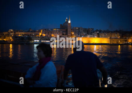 Valletta, Malta. 19th October, 2017. Commuters with the cityscape of Valletta behind them, as they travel on the - Stock Photo