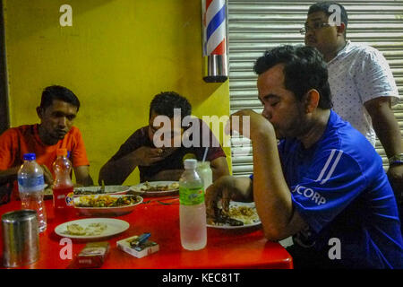 Kuala Lumpur, Selangor, Malaysia. 19th Nov, 2016. Syahrul having a dinner with his friends after he closed the grocery.Malaysia - Stock Photo