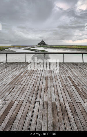 A distant view of Mont Saint Michel and storm clouds from the river Couesnon barrage in Normandy France - Stock Photo