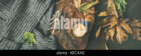 Autumn coffee concept with leaves and grey sweater, wide composition - Stock Photo