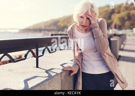 Elderly woman suffering from migraine on bridge - Stock Photo