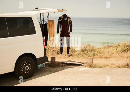 A surfers van parked at the beach with a wetsuit hanging outside to dry - Stock Photo