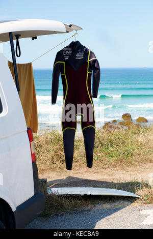 A surfers van parked at the beach with a wetsuit hanging outside to dry. - Stock Photo