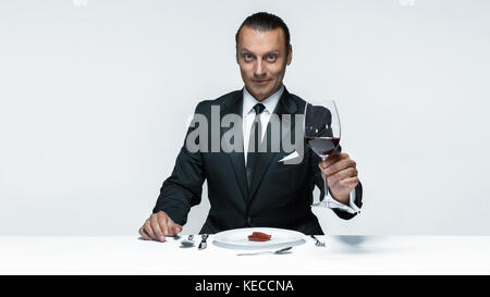 Bloody Halloween theme: crazy man with a knife, fork and meat - Stock Photo