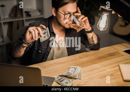 man drinking whiskey with pile of cash - Stock Photo